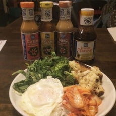 Kimchi, fried egg, cauliflower, and lettuce with four types of Soy Vay® Sauces